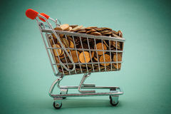 Shopping trolley with coins. On a green background Stock Image