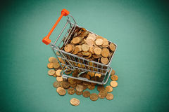 Shopping trolley with coins. On a green background Stock Images