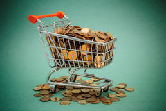 Shopping trolley with coins. On a green background Royalty Free Stock Photo