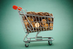 Shopping trolley with coins. On a green background Royalty Free Stock Images