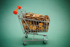 Shopping trolley with coins Stock Image