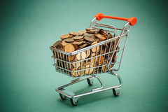 Shopping trolley with coins Stock Images