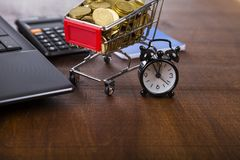 Shopping trolley with coins,  laptop and alarm clock Stock Photography