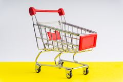 Shopping trolley on colorful background stock images