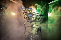 Shopping trolley on dark toned foggy background with some copy space. Empty shopping trolley on dark toned foggy background with some copy space. Financial Royalty Free Stock Images