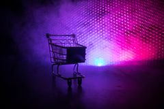 Shopping trolley on dark toned foggy background with some copy space. Empty shopping trolley on dark toned foggy background with some copy space. Financial Royalty Free Stock Image