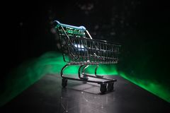 Shopping trolley on dark toned foggy background with some copy space. Empty shopping trolley on dark toned foggy background with some copy space. Financial Stock Image
