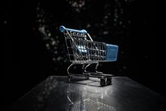 Shopping trolley on dark toned foggy background with some copy space. Empty shopping trolley on dark toned foggy background with some copy space. Financial Royalty Free Stock Photos