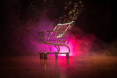 Shopping trolley on dark toned foggy background with some copy space. Empty shopping trolley on dark toned foggy background with some copy space. Financial Stock Images