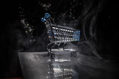 Shopping trolley on dark toned foggy background with some copy space. Empty shopping trolley on dark toned foggy background with some copy space. Financial Stock Photo