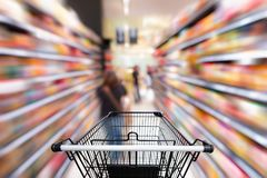 Shopping trolley in department store with goods shelf background.  Stock Photo