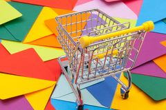 Shopping trolley and different envelopes on the desk. Shopping trolley and different colored envelopes on the table Stock Photos