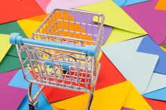 Shopping trolley and different envelopes on the desk. Shopping trolley and different colored envelopes on the table Royalty Free Stock Photography