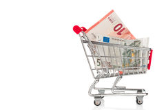 Shopping trolley with Euro banknotes. Isolated on white Royalty Free Stock Photography