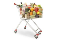Shopping trolley filled with different food products, fruits and vegetables stock photos