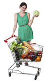 Shopping trolley filled food, young woman is holding a cabbage. Smiling Caucasian girl in a green dress 19 years old holding a cabbage standing near a shopping Royalty Free Stock Photo