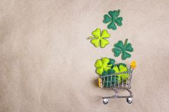 Shopping trolley with four-leaf clover on brown paper background Royalty Free Stock Photography