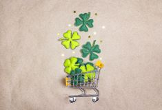 Shopping trolley with four-leaf clover on brown paper background Stock Photos
