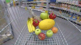 Shopping trolley with fresh vegetables and fruits moving through supermarket stock video