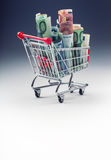 Shopping trolley full of euro money - banknotes - currency. Symbolic example of spending money in shops, or advantageous purchase Stock Photos