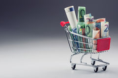 Shopping trolley full of euro money - banknotes - currency. Symbolic example of spending money in shops, or advantageous purchase Royalty Free Stock Photography