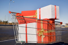 Shopping trolley full of gifts. Cart store with shopping in a parking lot Stock Image
