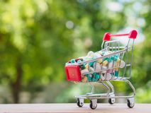 Shopping trolley full of medicine with pills and capsules on bok. Eh background. Healthy and medical concept Stock Photography