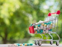 Shopping trolley full of medicine with pills and capsules on bok. Eh background. Healthy and medical concept Stock Photo