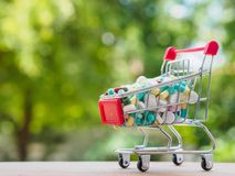 Shopping trolley full of medicine with pills and capsules on bok. Eh background. Healthy and medical concept Stock Photos