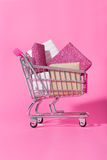Shopping trolley full of wrapped gifts on pink background Stock Photography