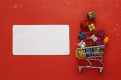 Shopping trolley with gift boxes and blank label for text on red Stock Photos