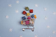 Shopping trolley with gift boxes on blue background. Royalty Free Stock Photo