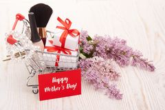 Lilac flowers and gifts on shopping trolley. Shopping trolley with gift boxes and brenches of Lilac on a wooden background. Greeting card. Mothers day. Top view Royalty Free Stock Photos