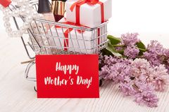 Lilac flowers and gifts on shopping trolley. Shopping trolley with gift boxes and brenches of Lilac on a wooden table on white background. Greeting card Royalty Free Stock Images