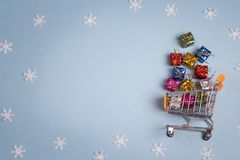 Shopping trolley with gift boxes and cope space on blue backgrou Stock Photography