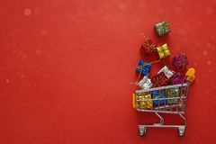 Shopping trolley with gift boxes and cope space on red backgroun Stock Photos