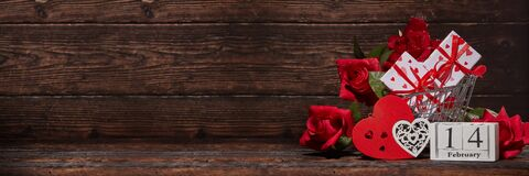 Free Shopping Trolley, Gifts, Hearts On Brown Wooden Background. 14 February. Valentine`s Day. Extra Wide Panorama Banner Background Royalty Free Stock Photos - 169025468