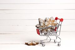 Shopping trolley with gingerbread snowflakes and cope space on w Stock Image
