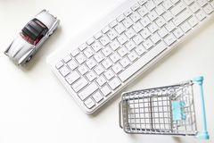 Shopping trolley, keyboard and toy car. Overhead image of computer keyboard, silver colored toy car and toy shopping trolley with wire basket royalty free stock photos