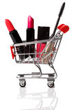 Shopping trolley with make-up products inside. Over white background Stock Photos