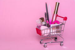 Shopping trolley with makeup on a pink background. Perfume, brush, mascara Royalty Free Stock Photography