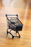 Shopping trolley. Metal shopping trolley on wood background Royalty Free Stock Photos
