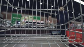 Shopping trolley is moving quickly along aisles in supermarket, shelves with food, drinks and goods are visible through. Cart grille. Shopping, sale and stock footage