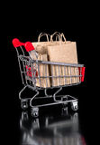 Shopping trolley with paper bags is isolated on black background Stock Photography