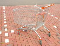 Shopping trolley in parking bay. Stock Photos