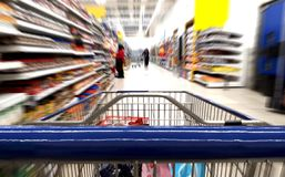 Shopping trolley push cart close up in supermarket aisle. Grocery shopping trolley push cart close up in supermarket aisle Royalty Free Stock Images