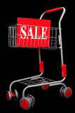 Shopping trolley with sale sign. On black background Stock Photography