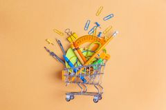 Shopping trolley with school supplies on yellow background. Flat. Lay, top view. Back to school concept Royalty Free Stock Images