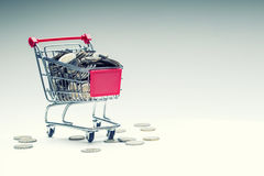 Shopping trolley. Shopping cart. Shopping trolley full of euro money - coins - currency. Symbolic example of spending money Royalty Free Stock Photo