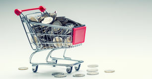 Shopping trolley. Shopping cart. Shopping trolley full of euro money - coins - currency. Symbolic example of spending money. Royalty Free Stock Photos